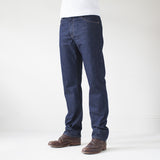 angle: resin rinse  A model wears Raleigh Denim Workshop Alexander work fit jeans with a dark wash, front view