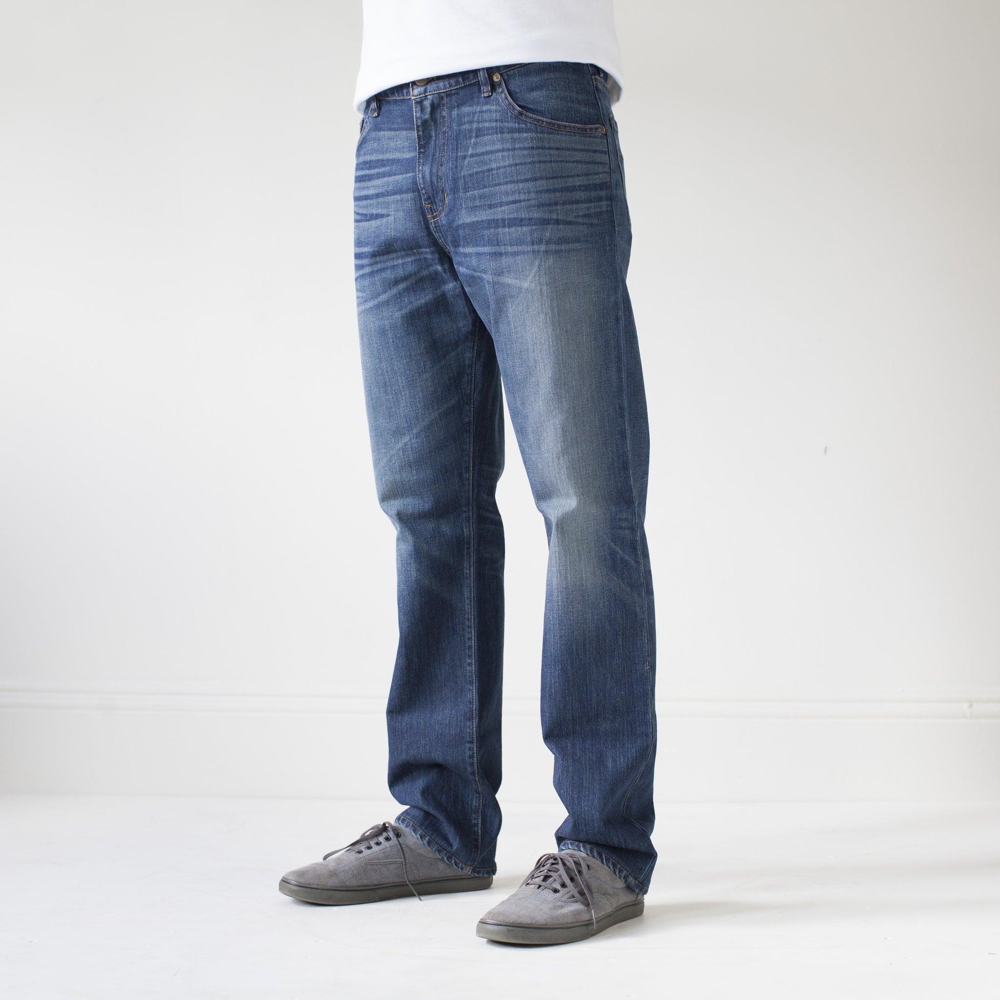 angle: 319  A model wears Raleigh Denim Workshop Alexander work fit jeans in the 319 wash, side view