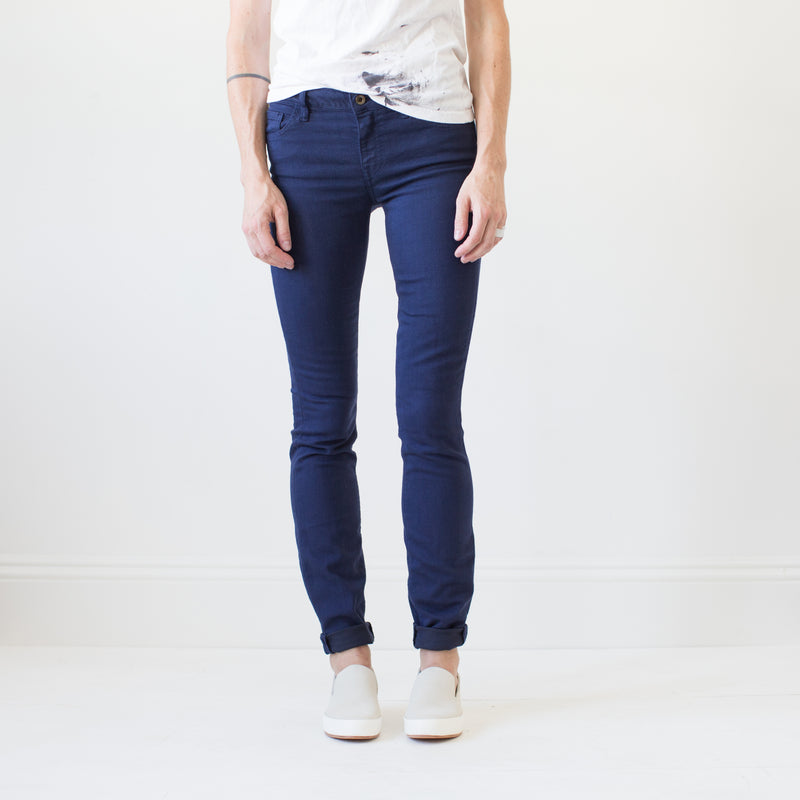angle hover: navy  A model wears Raleigh Denim Workshop Surry mid-rise thin fit jeans in dark navy, front view