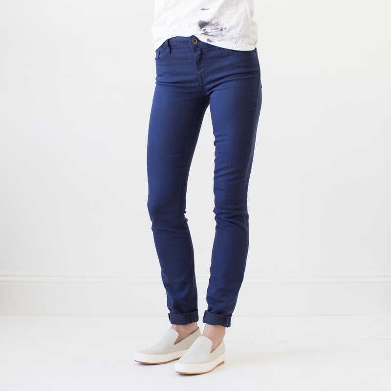 angle: navy  A model wears Raleigh Denim Workshop Surry mid-rise thin fit jeans in dark navy, front view