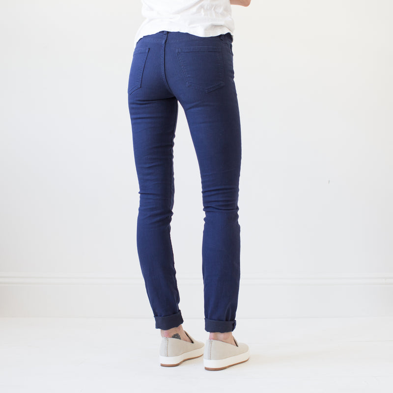 angle: navy  A model wears Raleigh Denim Workshop Surry mid-rise thin fit jeans in dark navy, back view