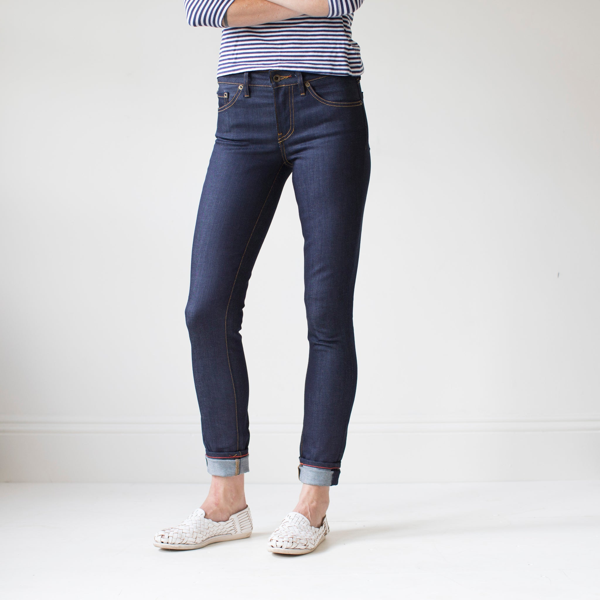 angle: indigo  A model wears Raleigh Denim Workshop Surry mid-rise thin raw dark jeans, front view