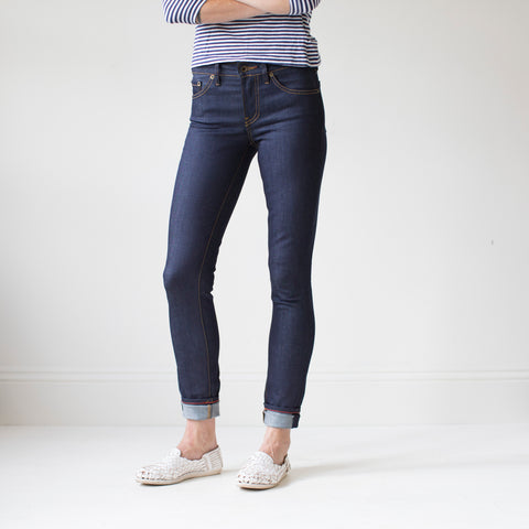 angle: indigo | A model wears Raleigh Denim Workshop Surry mid-rise thin raw dark jeans, front view
