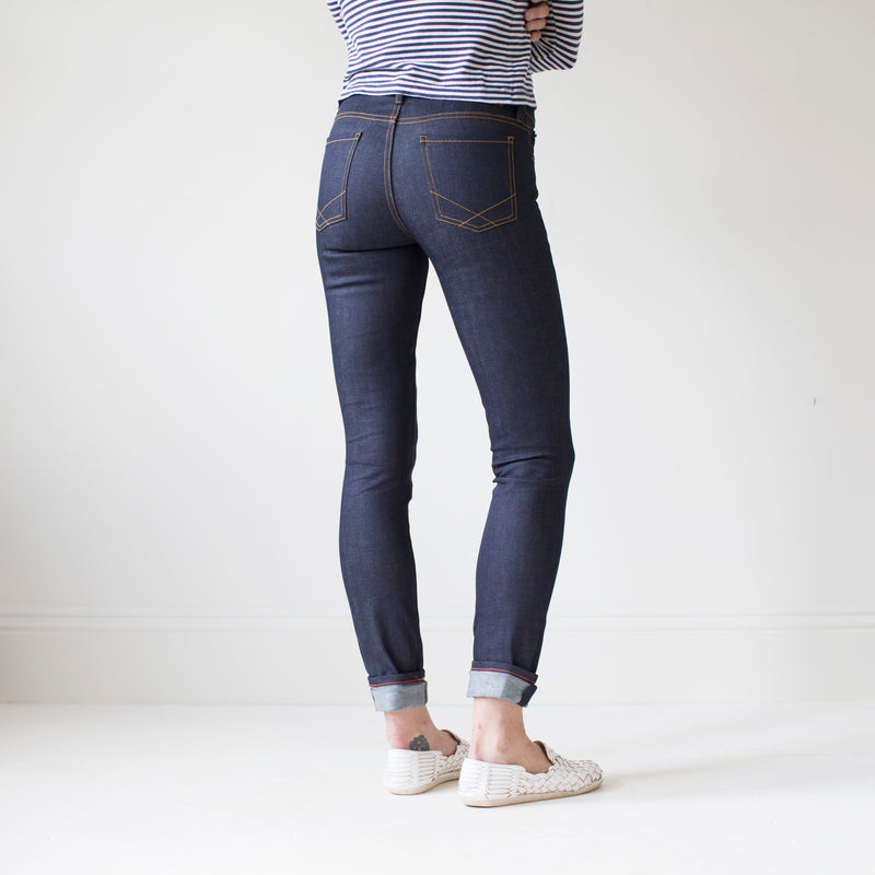 angle hover: indigo  A model wears Raleigh Denim Workshop Surry mid-rise thin raw dark jeans, back view