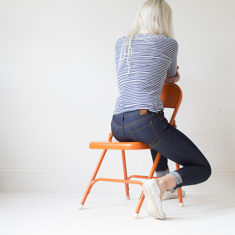 angle: indigo  A model wears Raleigh Denim Workshop Surry mid-rise thin raw dark jeans, back view