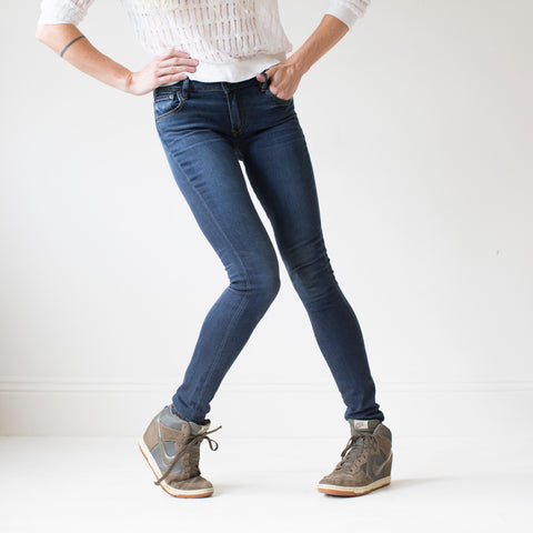 angle: saucepan | A model wears Raleigh Denim Workshop Surry mid-rise thin jeans in a dark wash, front view