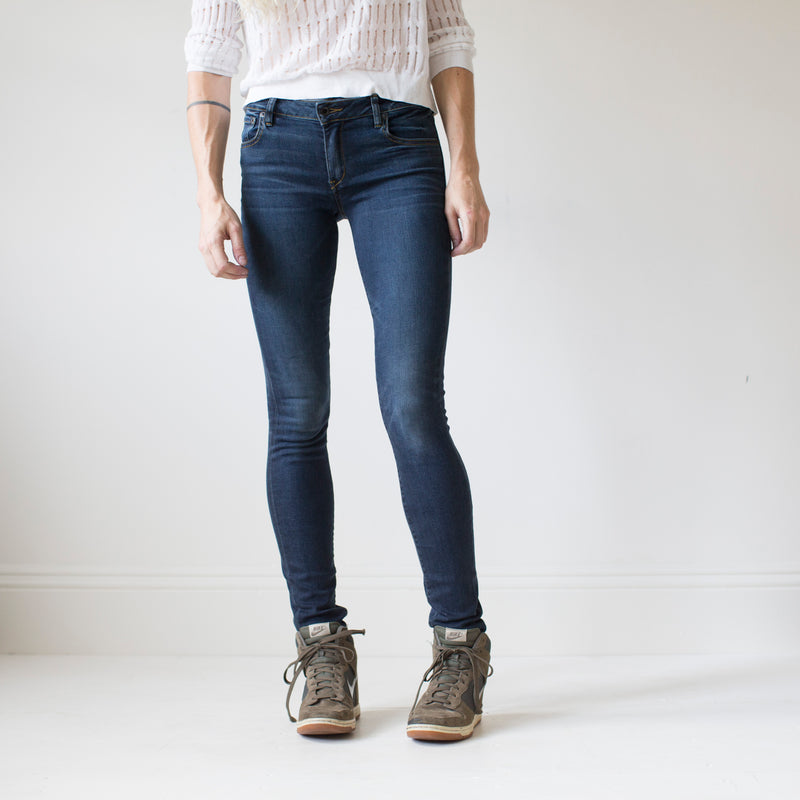 angle hover: saucepan  A model wears Raleigh Denim Workshop Surry mid-rise thin jeans in a dark wash, front view