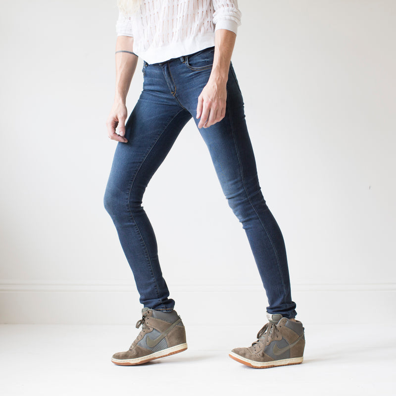angle: saucepan  A model wears Raleigh Denim Workshop Surry mid-rise thin jeans in a dark wash, front view