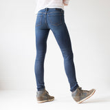 angle: saucepan  A model wears Raleigh Denim Workshop Surry mid-rise thin jeans in a dark wash, back view