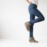 angle: saucepan  A model wears Raleigh Denim Workshop Surry mid-rise thin jeans in a dark wash, side view