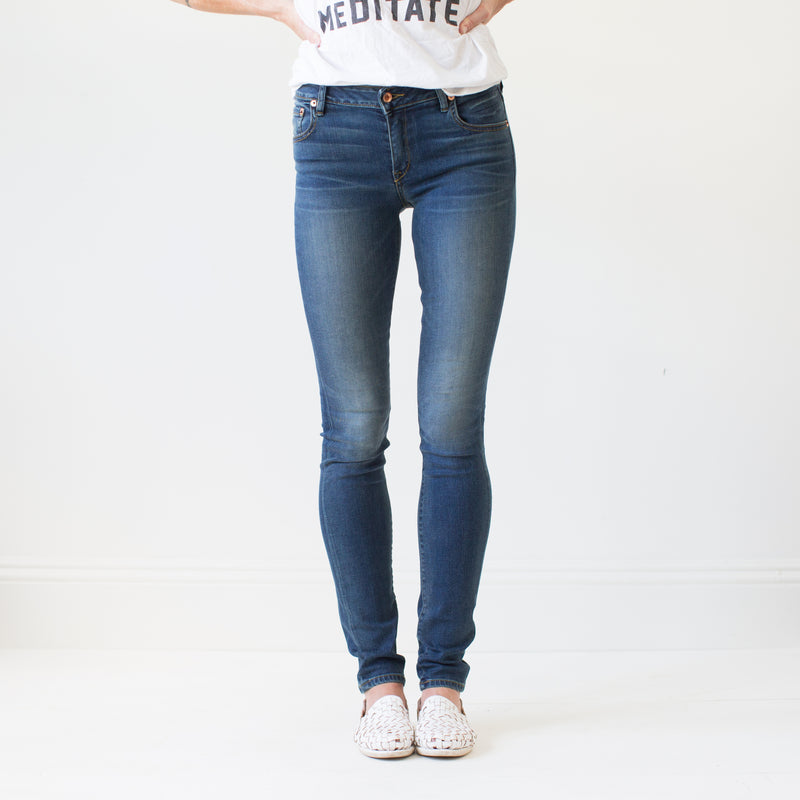 angle: vintage  A model wears Raleigh Denim Workshop Surry mid-rise thin fit vintage wash jeans, front view