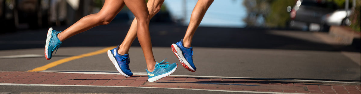 Man and woman running on pavement in Hoka One One Arahi running shoes