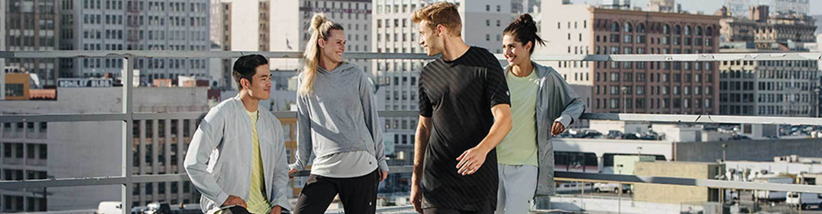 Group of people wearing ASICS athletic running apparel in front of city skyline