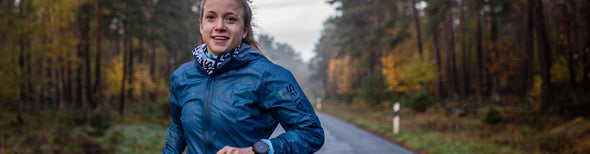 Woman on road surrounded by forest in Salomon running gear