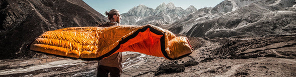 Man camping outdoors with orange sleeper bag