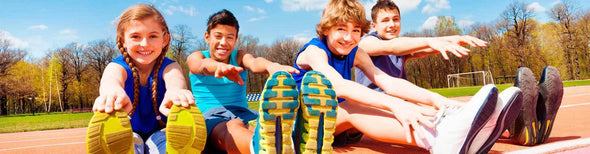 Smiling kids stretching in running shoes on track