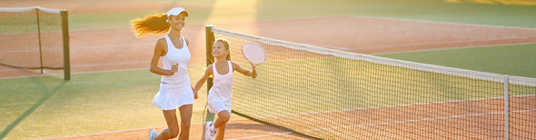 Woman and child on tennis court together