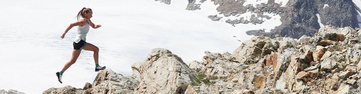 Woman running in On Running apparel in front of mountains