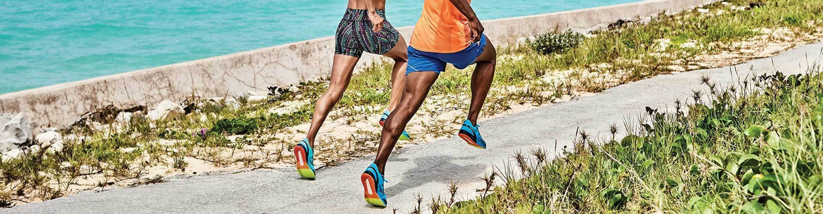 Man and woman running by the ocean in Saucony running shoes and athleticwear