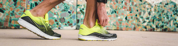 Man lacing up Saucony running shoes