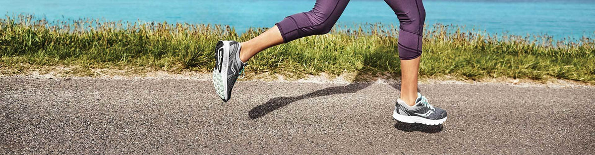 Woman running by ocean in Saucony running shoes