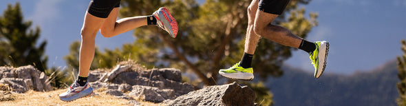Man and woman running in New Balance trail running shoes
