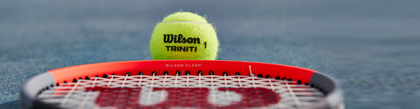 Woman serving tennis ball with Wilson tennis racquet