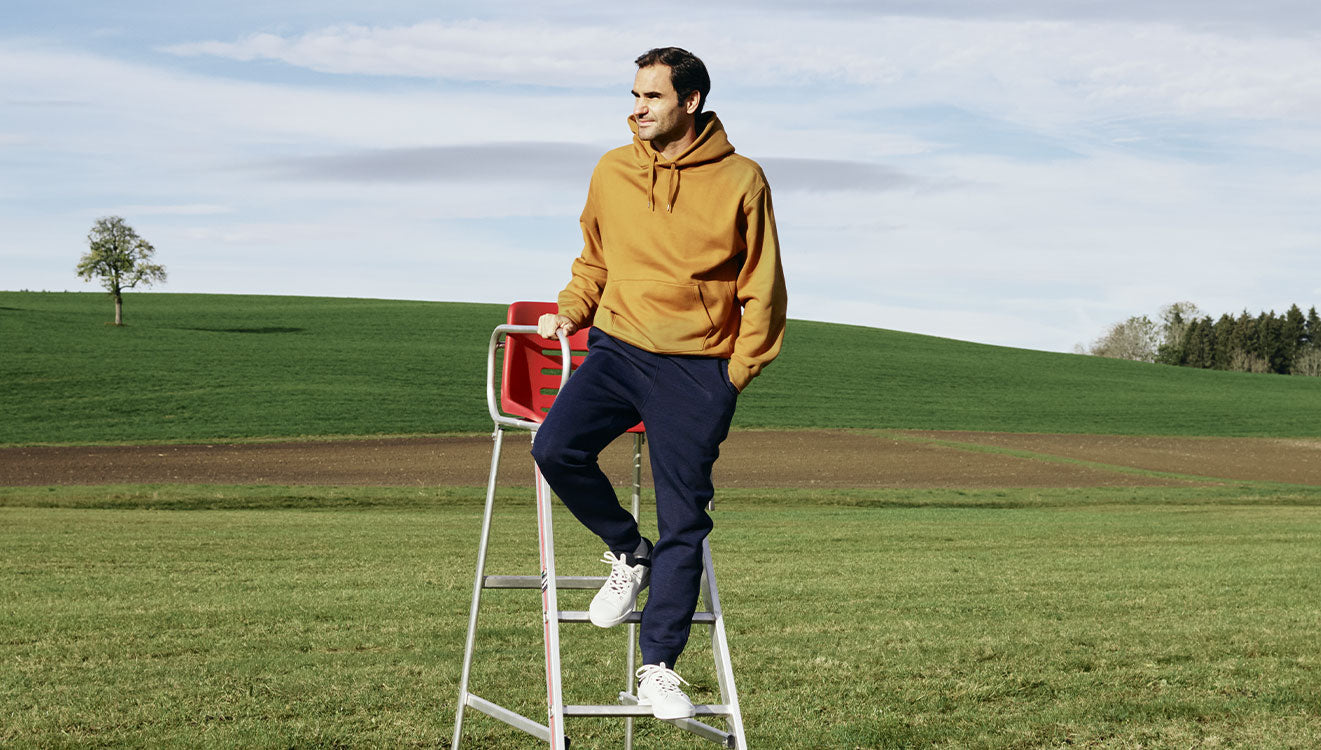 Roger Federer in grassy field in the On The Roger Federer Advantage tennis shoes