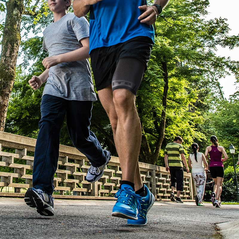 Man running in park with OS1ST compression leg sleeve