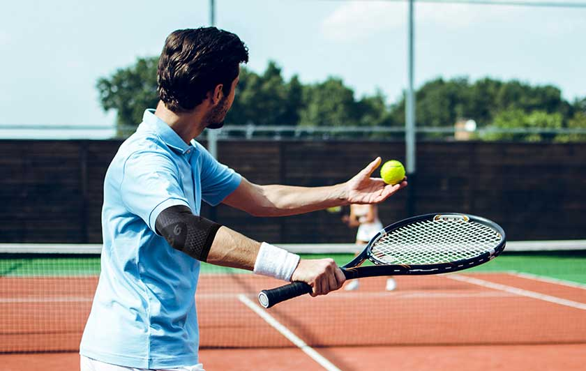 Man playing tennis in OS1ST elbow compression sleeve