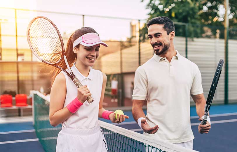 Happy man and woman on tennis court