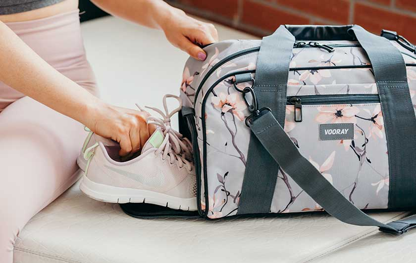 Woman putting pink Nike sneakers in gray cherry blossom Vooray bag