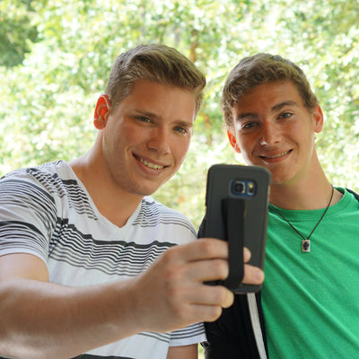 Two young men holding mobile phone using a LoveHandle Phone Grip.