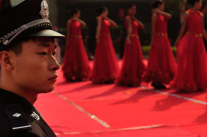 Cop with Red Dancers in Background, Pingyao