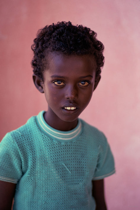 Young Boy in Green Against Pinkish Wall, Somalia