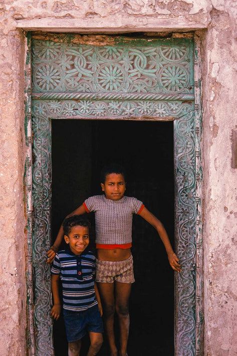 Two Kids in Door Frame, Green Background, Somalia