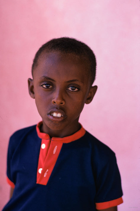 Young Boy in Blue and Red Against Pinkish Background, Somalia
