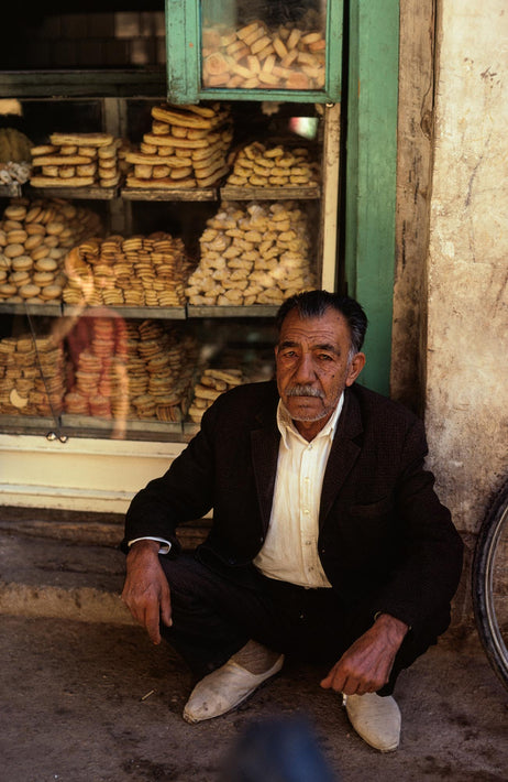 Man Squatting in front of Bakery Window, Iran