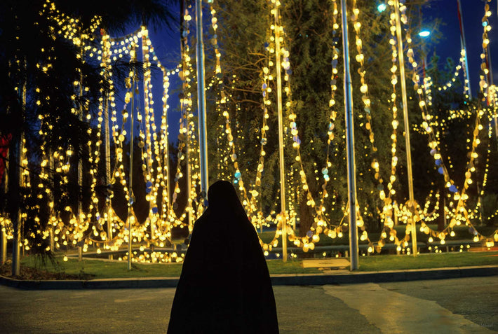 Woman in Chador Against Yellow Lights, Iran