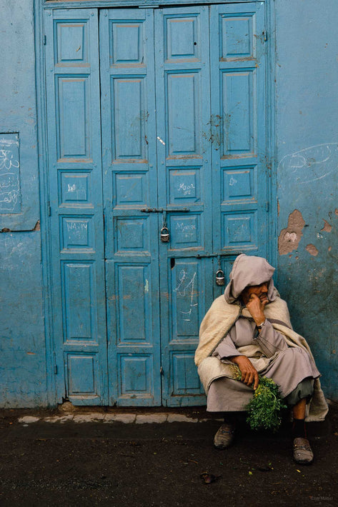 Man Holding Greens Sitting Against Blue Paneled Door, Marrakech
