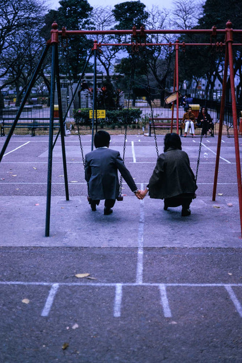 Couple Holding Hands on Swings