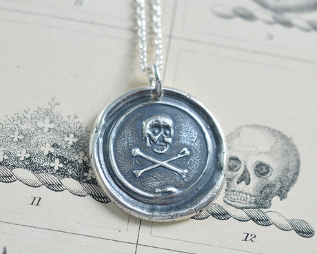 skull and crossbones surrounded by ouroboros wax seal necklace