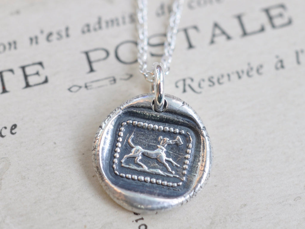 dog carrying a letter wax seal necklace