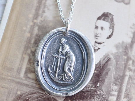 woman leaning on anchor wax seal necklace