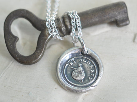 wax seal necklace with a man struggling through the world - by honesty