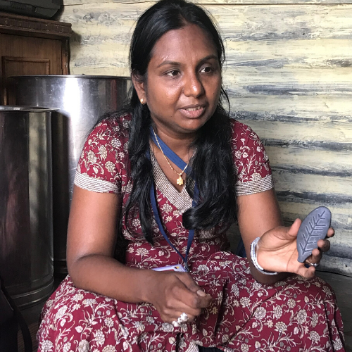 Woman in maroon dress holding Lucky Shakti Leaf- a natural iron supplement safe for whole family