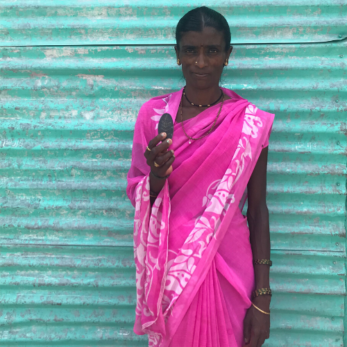 Woman in pink saree holding Lucky Shakti Leaf- a natural iron supplement safe for whole family