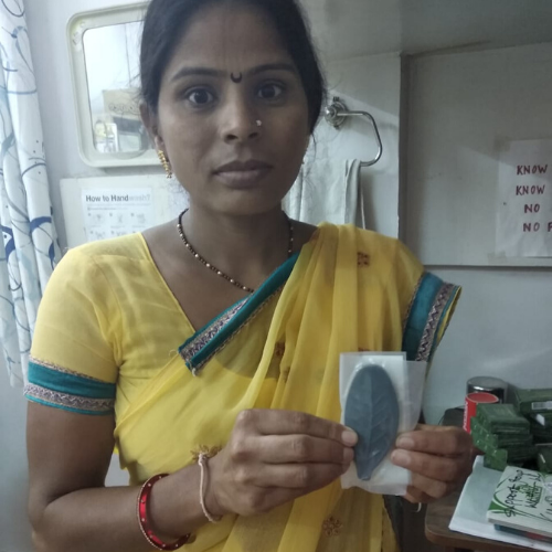 Woman in yellow saree holding Lucky Shakti Leaf- a natural iron supplement safe for whole family