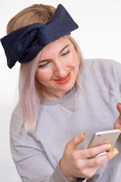 Beautiful woman with blonde hair and a Lysande headband on her phone