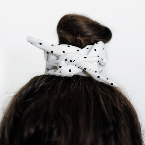 Brown hair tied in an updo with a black and white polka dot wire-framed bandana wrapped around the bun.